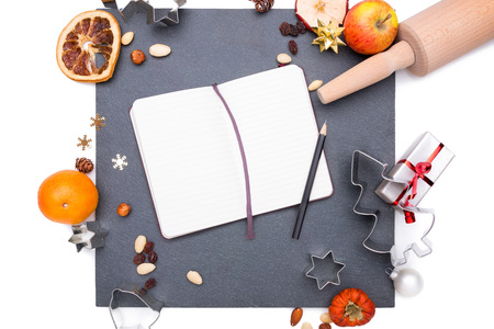 inscribe: Plate of slate with a notebook and christmas things around it.