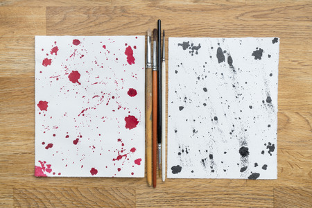 two piece: Two piece of papers spotted with ink and brushes in a wooden background Stock Photo