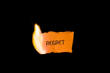 ignited: A burning piece of paper with the word  regret  written on it isolated on a black background