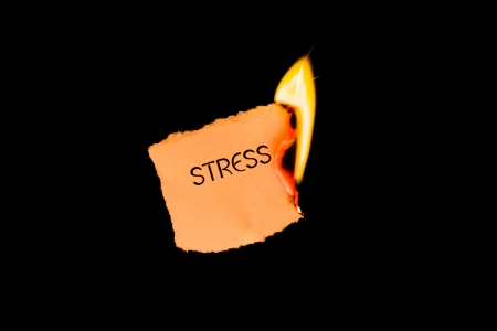 ignited: A burning piece of paper with the word  stress  written on it isolated on a black background