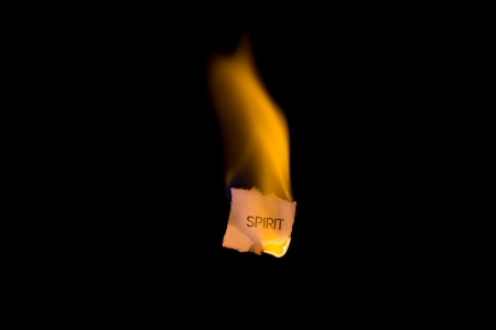 ignited: A burning piece of paper with the word spirit on it Stock Photo