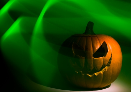 A jack-o-lantern in deep shadow with green wisps curling around it