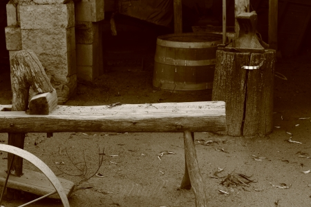 wheel barrel: Rustic scene of an old workshop with barrel, bench and wagon wheel