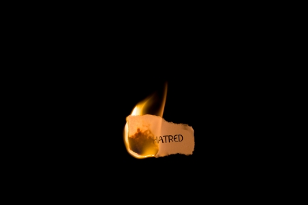 ignited: A burning piece of paper with the word hatred on it isolated on black with copy space