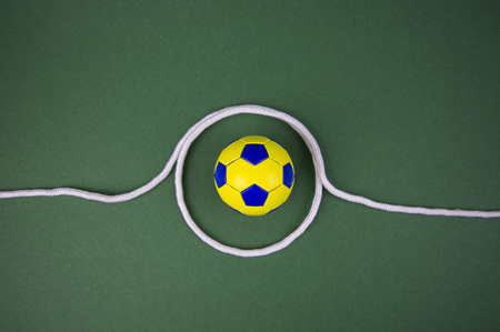 soccer ball on a green background, yellow-blue diamonds, with space for adding text Stockfoto