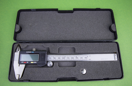 caliper with digital screen on a green background, there is free space to fill the text Archivio Fotografico