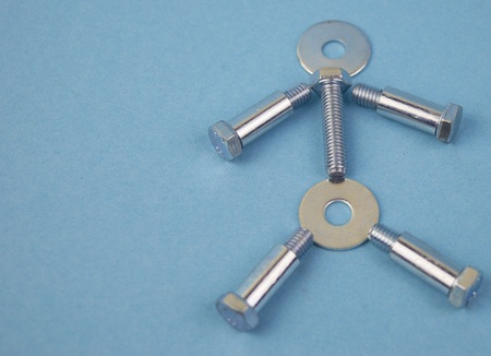 bolts, nuts, bushings on a blue background with empty space to fill