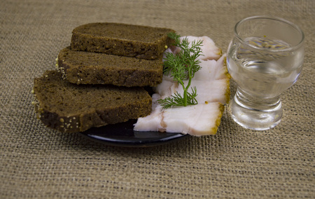 A glass of vodka, lard, bread on the table. There is a place to fill the text. Imagens