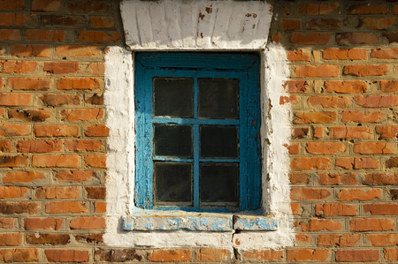 The window of the house in the brick wall is red, there is a place to fill Stock Photo