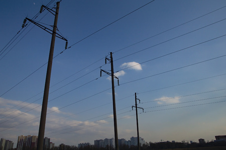 high voltage power line against a blue sky with clouds