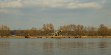 barge on the river in the spring on a sunny day against the blue sky