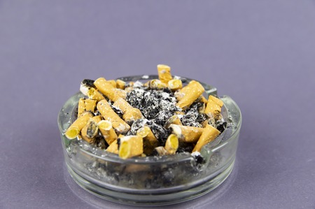 overflowing ashtray with cigarette butts and ash on a gray background Imagens