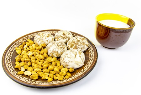 Gingerbread cookies and peanuts on a platter with a cup of milk, on a white background. There is free space for text.