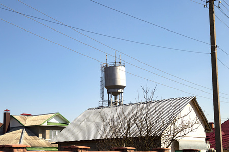 Water tower with mobile communication transmitters above the houses against the blue sky
