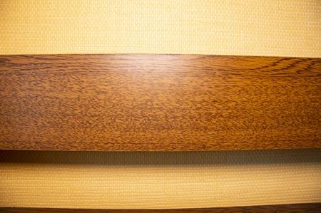 Houten plank tegen een beige muur. Achtergrond. Plaats voor tekst.