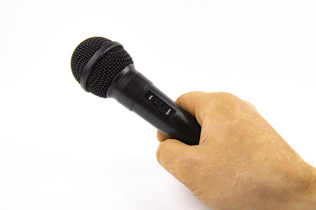 Black microphone in a man's hand on a white background. Place for text. Stock Photo