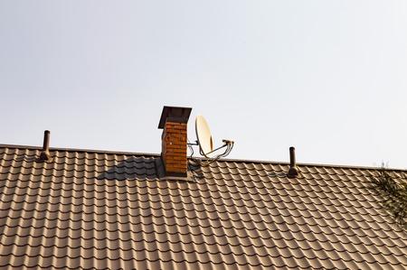 Satellite TV antenna near the chimney pipe on the roof of a house under a blue sky Zdjęcie Seryjne