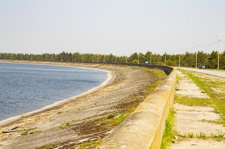 Water horizon, concrete embankment near the water - background