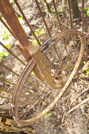 Old rusty bicycle wheel without tire and chamber