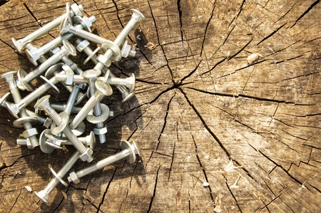 Bolts, nuts, washers on the wooden surface of an old stump 免版税图像