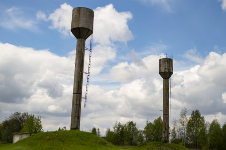 Water tower against the blue sky with white clouds. Industrial landscape.