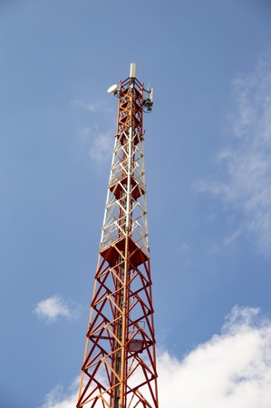 Tower mobile operator against the blue sky with white clouds. Cellular base station. Banco de Imagens