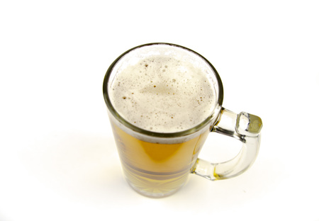 Glass beer mug with foam on a white background Imagens