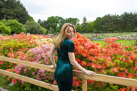 Girl blonde in green on a background of flowers in the park Stockfoto