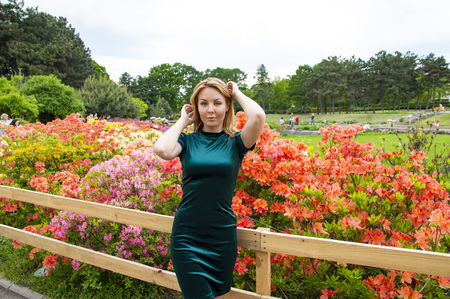 Girl blonde in green on a background of flowers in the park