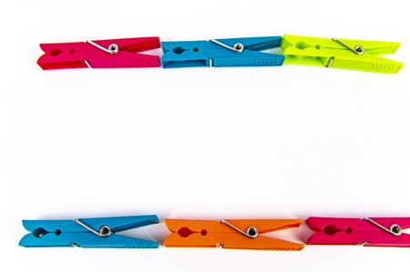 Colored clothespins on a white background, free space for writing text.
