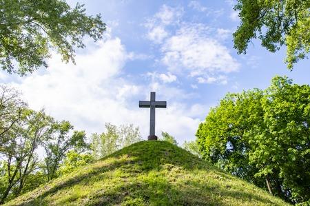 Christian cross on a green hill hill under a cloudy sky on a sunny day Reklamní fotografie