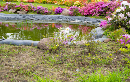 Artificial lake surrounded by flowers in the garden. Background.