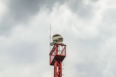 Tower with antenna connection on the background of a cloudy sky. Technology.