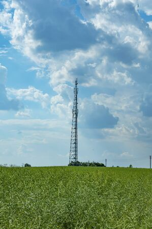 Tower of mobile communications against the blue sky with white clouds. Technology.