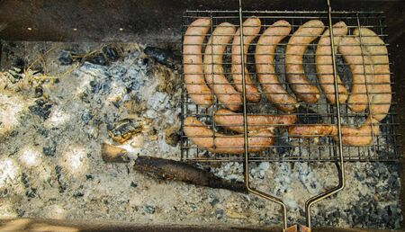 Bavarian grilled sausages on the grill - cooking