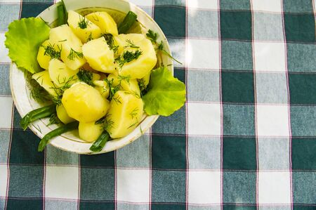 Potatoes with herbs in a plate on a tablecloth in a cage. Background. Reklamní fotografie