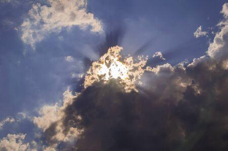 Die Sonnenstrahlen durchbrechen die Wolken am Himmel. Hintergrundbild.