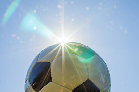 Soccer ball on the background of the sun. Glare of sunlight. Place for text. Background image.