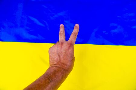 Victory hand gesture on the background of the Ukrainian flag - Independence Day. Background. 版權商用圖片