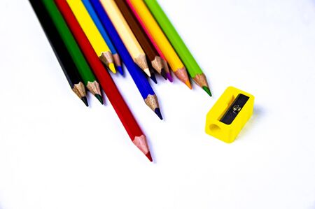 Multi-colored pencils for drawing with a sharpener on a white background. School. Background. Place for text.