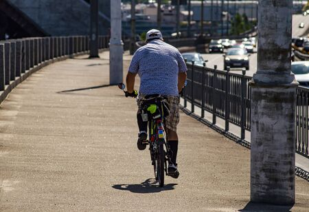 A man rides a bicycle. Back view. Sports and recreation. Lifestyle.
