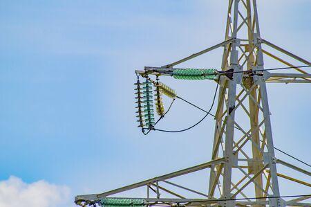 Wieża linii wysokiego napięcia na tle błękitnego nieba. Technologia.