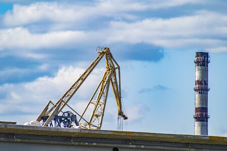 Dock crane and industrial chimney against a blue sky with clouds. Industrial landscape.