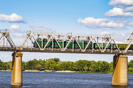 Railway bridge over the river with a train against a blue sky. Railway. Background image. Фото со стока