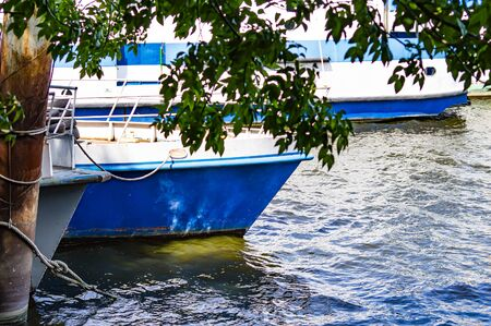 Old white pleasure boats moored on the river. Water transport.