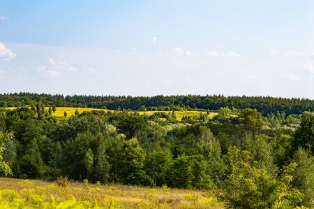 Natural hilly landscape against the blue sky. Outdoors. Horizon. Фото со стока