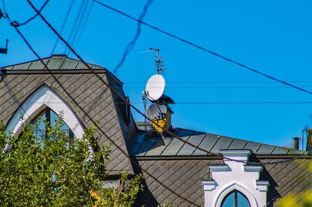 Satellite dishes on the roof of the house. Blue sky. Technology.