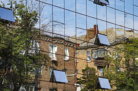 Reflection of houses in the mirrored windows of an office building. Background image.