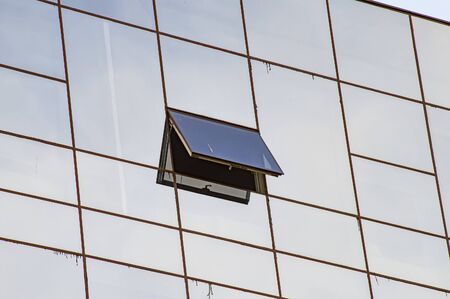 An open window in the mirrored glass of an office building. Background image.