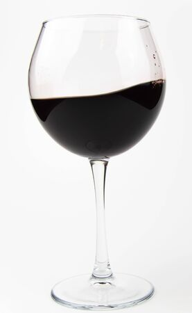 A splash of red wine in a glass goblet. Background. Place for text.